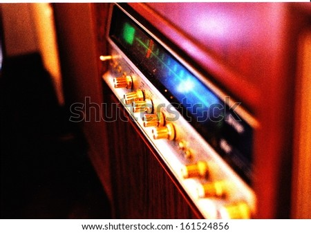 An older style radio with many knobs. - stock photo