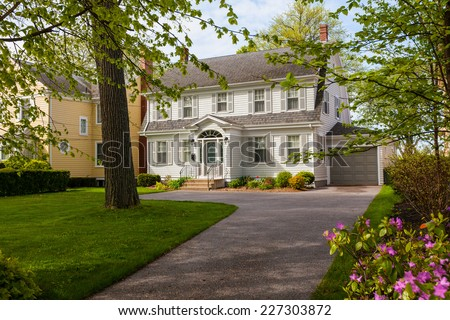 An older style traditional home with a springtime garden. - stock photo