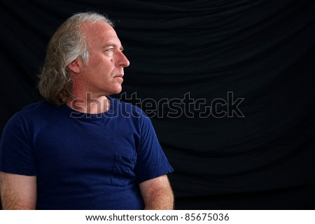 An older white male is looking towards copy space in blue t shirt against black background. - stock photo