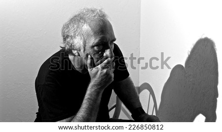 An older white man is looking away with a concerned look on his face and covering his mouth. - stock photo