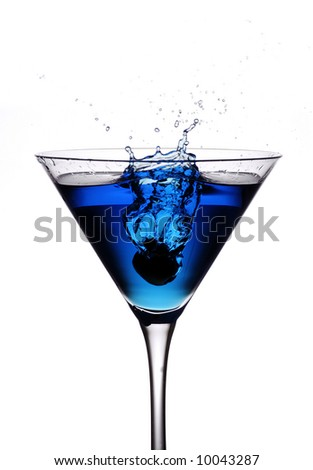 an olive being dropped from height into a blue cocktail - stock photo