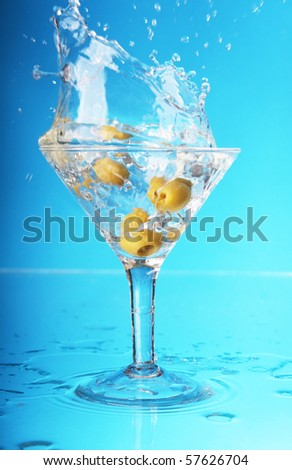 an olive splashing into a martini - stock photo