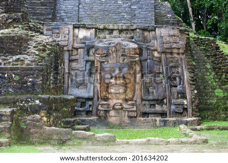 An Olmec style face adorns the side of the Mask Temple wall at the Mayan site of Lamanai in Belize. - stock photo