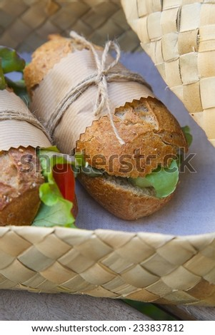 An open-air  express lunch for a vegetarian- whole grain rolls with fresh vegetables. Rolls are hidden in the woven birch basket