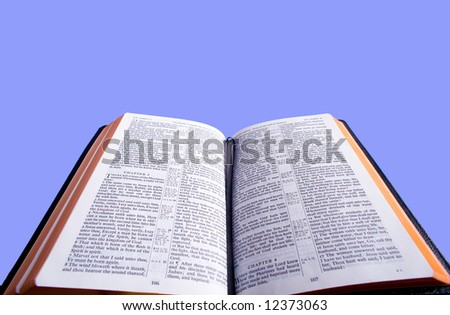 An open Bible in front of a blue sky background with copy space.  Bible version is the King James version of the bible which is in the public domain
