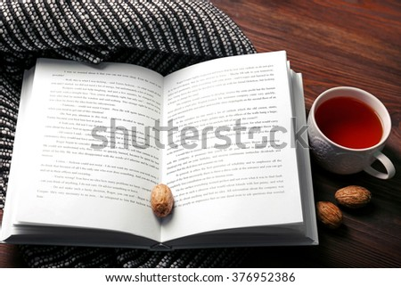 An open book, a cup of tea, nuts and a blanket on the floor, close-up