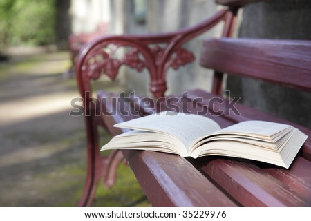 An open book on a park bench seat. - stock photo