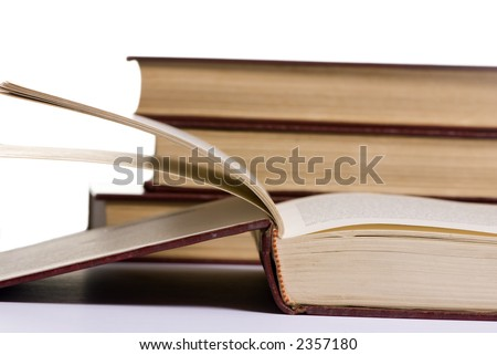 An open book on a table with a pile of other books in the background....study hard. - stock photo