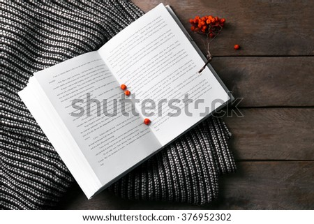 An open book, rowan berries and a blanket on the wooden background