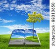 An open book with green natural landscape inside - stock photo