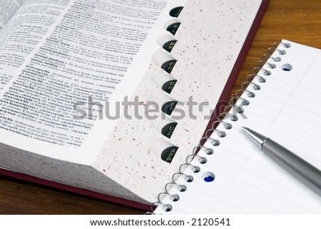 An open dictionary with a notebook and pen - stock photo