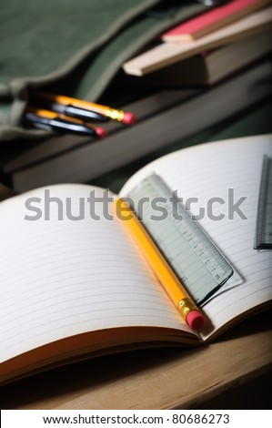 An open exercise book on table with pencil and ruler.  Open satchel in background.  Vertical (portrait) orientation.