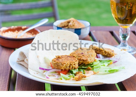 An open falafel wrap with salad served on a table outside - stock photo