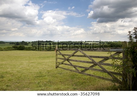 An open farm gate leading to a field - stock photo