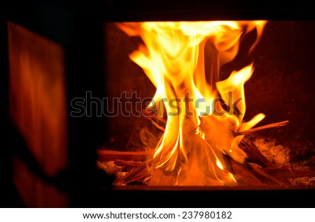 An open fireplace door with warm fire flame during a cold winter day. - stock photo