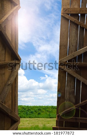 An open gate of a barn with a view of the sky and grass - stock photo