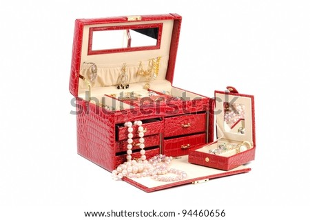 An open jewelery box with gold and platinum  jewelry   on a white background