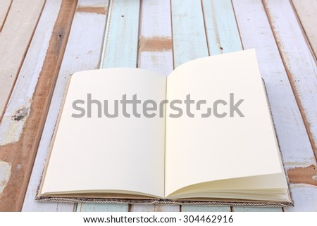 An open notebook on grunge retro wooden background - stock photo