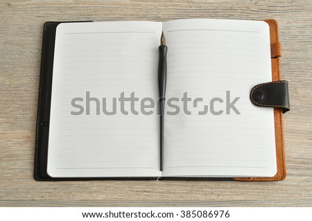 An open notebook with a fountain pen displayed on a table - stock photo
