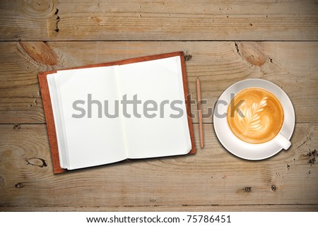 An open notebook with cup of coffee - stock photo