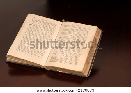 An open old German bible resting on a table awash in warm light