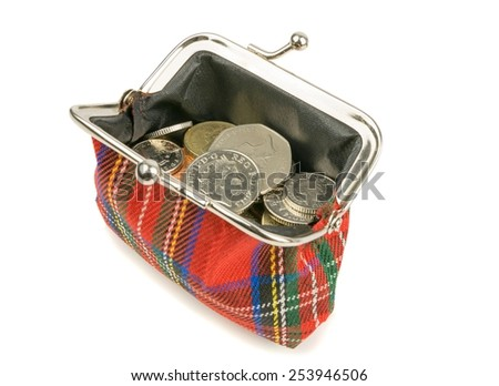 An open purse full of British money coins on a white background - stock photo