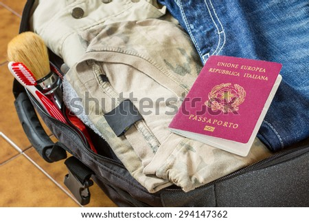 An open suitcase with clothes, personal effects and an italian passport on it - stock photo