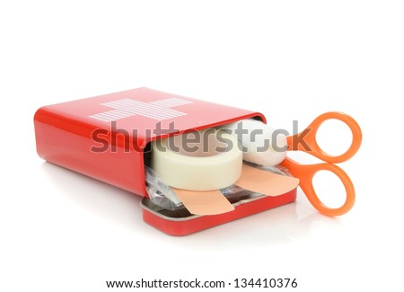 An open travel first aid kit lying on a white background - stock photo