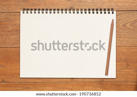 An Open vintage sketchbook or notebook with pencil on modern wooden table - stock photo