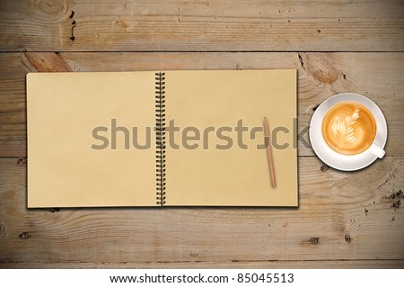 An Open Vintage Sketchbook with Pencil and a Cup of Coffee on Old Wooden Table - stock photo