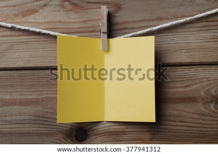 An opened, blank yellow greetings card,  pegged on to string against wood plank background - stock photo