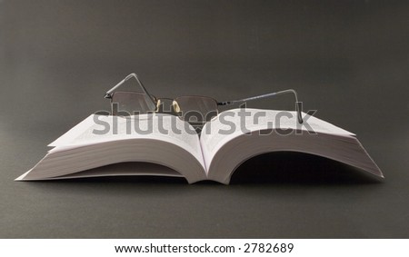 An opened book with a glasses on is