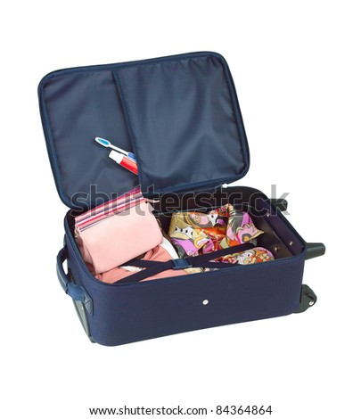 An opened suitcase packed with colorful cloth and cosmetic bag - stock photo