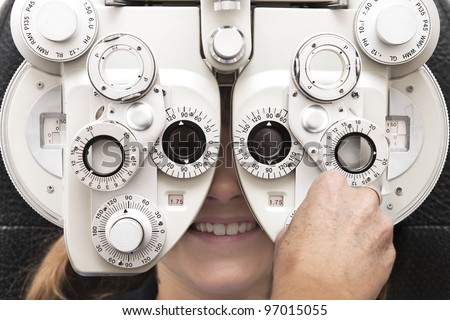 an optometrist adjusts the dials on the phoropter during an eye test - stock photo