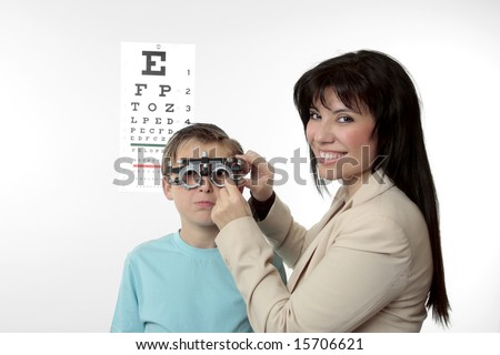 An optometrist putting trial frames on a child.  She is looking around and smiling. - stock photo