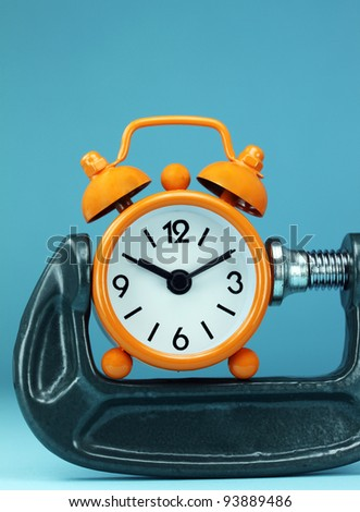 An orange alarm clock placed in a Grey clamp against a pastel purple background, asking the question do you manage your time effectively - stock photo