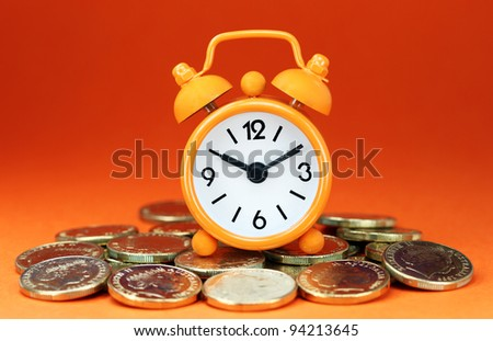 An orange colored  alarm clock placed in a Grey clamp against a pastel blue background, asking the question do you manage your time effectively. - stock photo