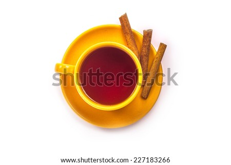 An orange cup of tea on saucer with cinnamon. View from above. Isolated on a white background. - stock photo