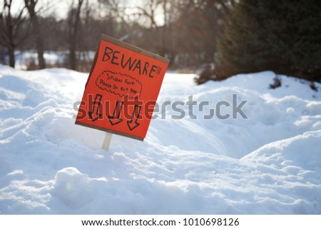 An orange sign made by children warning about the existence of a snow fort