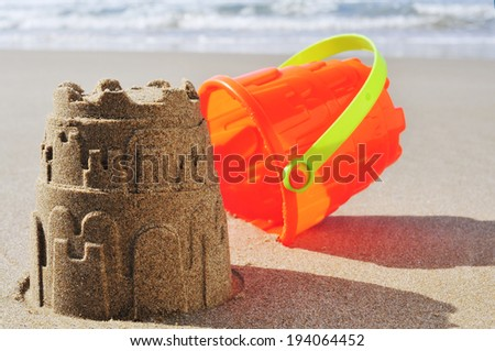 an orange toy bucket and a sandcastle on the sand of a beach - stock photo
