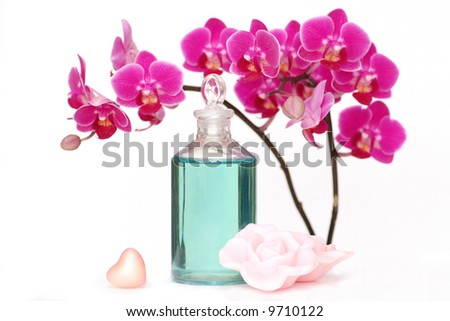 An orchid with a bottle of massage oil, heart and rose petal shaped soap. - stock photo