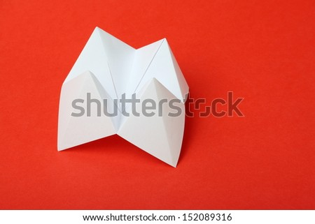 An origami fortune teller or cootie catcher made from blank white paper on a red background with room for your text. - stock photo
