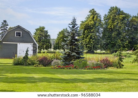 An ornamental garden with conifers and flowers in a rural farm setting. - stock photo
