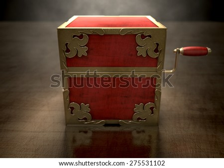 An ornate antique closed jack-in-the-box mad of red wood and gold trimmings on a dark studio background under a spotlight - stock photo