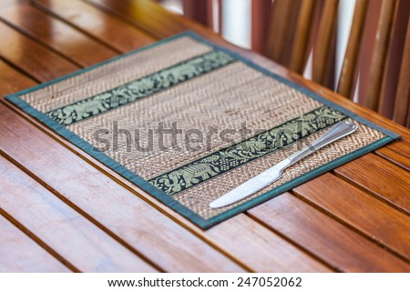 an ornated place mat in a thai restaurant with a knife - stock photo
