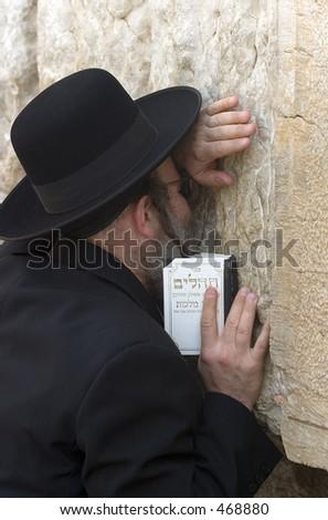 An orthodox man praying at the wailing wall - stock photo
