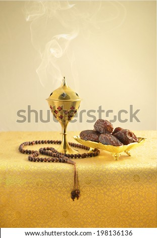 An oudh burner, islamic prayer beads and dates on golden background - stock photo