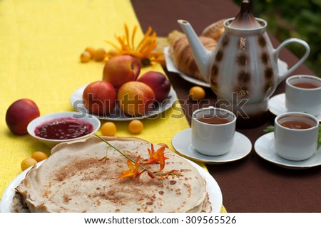 An outdoor composition with tea cups, a tea pot, a plate of pancakes, pastry, ripe fruit and field flowers on a bright yellow and brown table cloth  - stock photo