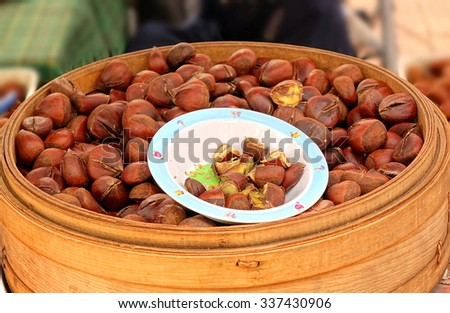 An outdoor vendor sells steamed chestnuts and offers samples in a bowl  - stock photo