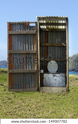 An outdoors toilet on the beach in New Zealand. - stock photo